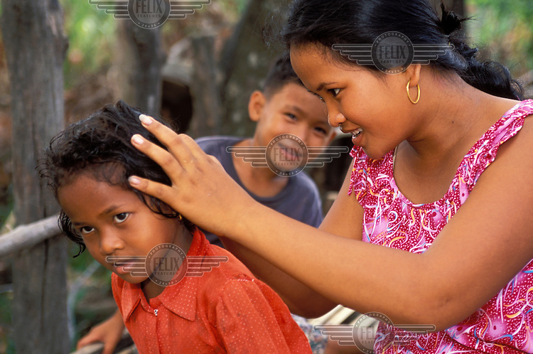 A mother checks her child's head for lice.