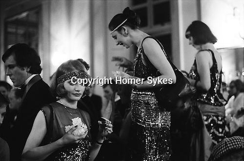 The Baddeley Cake, Theatre Royal Dury Lane, London. The cast for the play No No Nanette. England 1974.<br /> <br /> 17 JANUARY<br /> Baddeley Cake<br /> CATHERINE STREET, LONDON<br /> <br /> In the past, Twelfth Night was much more extensively celebrated than it is today when all that happens is the mundane removing and storing of the Christmas decorations to avoid bad luck in the ensuing year. In religious terms Twelfth Night is the feast of the Epiphany when Christ first revealed him-self to the Gentiles in the persons of the Three Wise Men, and the Christmas ceremonies are over. Formerly, the occasion was celebrated by merry-making,<br /> for instance with the ceremonial Twelfth Night cake.<br /> The Baddeley cake commemorates the pastry cook Robert Baddeley who, through the offices of Samuel Foote in appreciation of a fine dinner prepared by Baddeley, managed to secure a small part in a Drury Lane production. After this episode, rather than relapse into oblivion, he developed into a good actor and was the original Moses in Sheridan's School for Scandal. When he died in 1774 he left in his will one hundred pounds in 3 per cent funds for the making and baking of a cake. This was to be eaten, in his memory, every Twelfth Night by the cast after the performance at the Theatre Royal, Drury Lane. Except for the years of the First and Second World Wars the custom has carried on every year since his death. The photograph shows some of the cast from No No Nanette enjoying their Baddeley Cake.