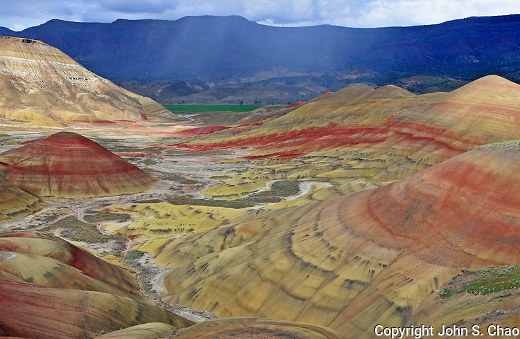 View down the valley between the Painted Hills National Monument, with backdrop of a distant raincloud.