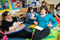 """A breastfeeding consultant giving advice to a mother who is breastfeeding her baby at a drop-in breastfeeding support centre.<br /> <br /> Image from the """"We Do It In Public"""" documentary photography project collection: <br />  www.breastfeedinginpublic.co.uk<br /> <br /> Dorset, England, UK<br /> 17/04/2013"""