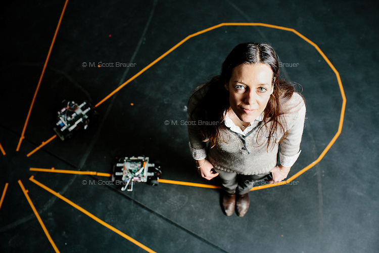 Seen in her multi-vehicle lab, Domitilla Del Vecchio is an Associate Professor in MIT's Department of Mechanical Engineering in Cambridge, Massachusetts, USA. She is also a member of the Synthetic Biology Center and the Control Networks Group.<br /> <br /> She is seen with small vehicle robots built by students. The vehicles can drive along a path marked on the floor and avoid collisions with one another because of the control system developed in the lab. The vehicles use cameras mounted near the ceiling to obtain position information. That information, along with speed information from the vehicles themselves, is transmitted to other vehicles on the track.