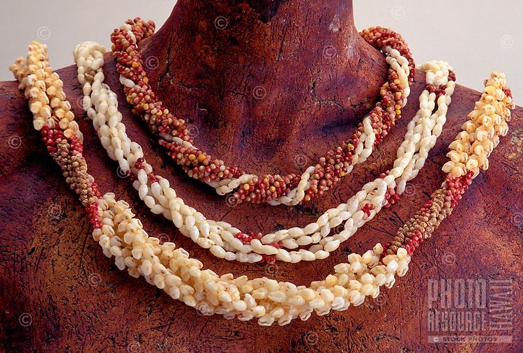 Three rare Niihau shell necklaces on statue figure