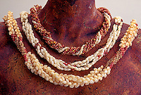 Three rare Niihau shell necklaces on statue figure