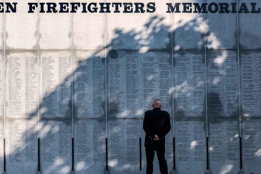 Firefighter reflects on lost collegues at the New York Firefighters Memorial, Albamy, New York, USA.