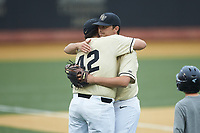 Wake Forest Demon Deacons senior pitcher Ben Casstevens (20) gets a hug from Rhyse Dee (42) as he walks off the field during the game against the Miami Hurricanes at David F. Couch Ballpark on May 11, 2019 in  Winston-Salem, North Carolina. The Hurricanes defeated the Demon Deacons 8-4. (Brian Westerholt/Four Seam Images)