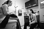 Young female internal medicine resident physician listens to young female patient seated on examination table in examination room