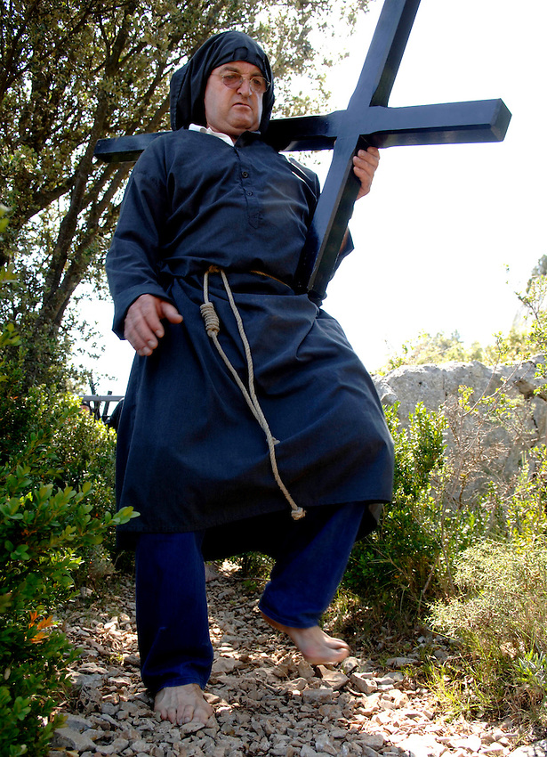 IRUNBERRI - LUMBIER, NAVARRE - JUNE 11: A barefoot penitent dressed in a black monk habit carries a heavy cross during the celebration of the 'Cruceros' brotherhood penitential pilgrimage to the 'Ermita de la Trinidad' on June 11, 2006 in Irunberri - Lumbier, Navarre.