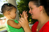 MR / Schenectady, NY. Mother (20) and her infant daughter (girl, 9 months, African American & Caucasian) clapping hands together. MR: Dal4, Dal6. ID: AL-HD. © Ellen B. Senisi