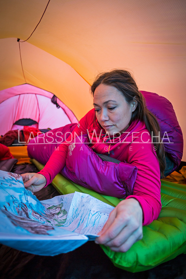 Female hiker looks over a map inside a tent, Iceland