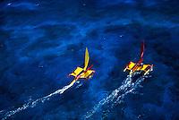 Two catamaran's sailing off the coast of The Big Island of Hawaii in blue water.