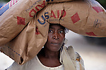 A woman carries food provided by a relief program in a camp in Grand-Goave, Haiti, for families left homeless by the January 2010 earthquake. The ACT Alliance has supported families in this camp with a variety of services, and has rebuilt a school beside the tent city.