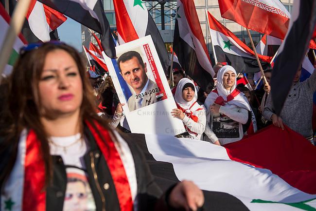 """250 bis 300 Menschen demonstrierten am Samstag den 31. Oktober 2015 in Berlin fuer die Unterstuetzung des syrischen Diktators Assad durch Russland. Sie trugen Fahnen Syriens, der ehemaligen Sowietunion, Russlands, Nordkoreas, der DDR, des Iran und Venezuelas, die sich """"alle zusammen gegen den Imperialismus zur Wehr setzen"""" wuerden. Russlands Praesident Putin wurde ausdruecklich fuer sein Militaerengagement gedankt, das Eingreifen der USA verurteilt.<br /> Im Bild: Eine Demonstrantin mit einem Portraitfoto des syrischen Diktators Assad auf dem er als Prasident bis zum Jahr 2021 bezeichnet wird.<br /> 31.10.2015, Berlin<br /> Copyright: Christian-Ditsch.de<br /> [Inhaltsveraendernde Manipulation des Fotos nur nach ausdruecklicher Genehmigung des Fotografen. Vereinbarungen ueber Abtretung von Persoenlichkeitsrechten/Model Release der abgebildeten Person/Personen liegen nicht vor. NO MODEL RELEASE! Nur fuer Redaktionelle Zwecke. Don't publish without copyright Christian-Ditsch.de, Veroeffentlichung nur mit Fotografennennung, sowie gegen Honorar, MwSt. und Beleg. Konto: I N G - D i B a, IBAN DE58500105175400192269, BIC INGDDEFFXXX, Kontakt: post@christian-ditsch.de<br /> Bei der Bearbeitung der Dateiinformationen darf die Urheberkennzeichnung in den EXIF- und  IPTC-Daten nicht entfernt werden, diese sind in digitalen Medien nach §95c UrhG rechtlich geschuetzt. Der Urhebervermerk wird gemaess §13 UrhG verlangt.]"""