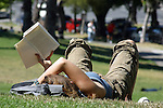 YOUNG WOMEN IN PARK RELAXES WITH BOOK