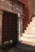 Arequipa, Peru. Carved door and window in a red painted wall with flowers in a pot.