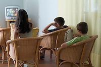 Three children watching television.