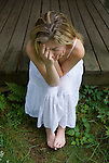 Blonde woman sitting on porch