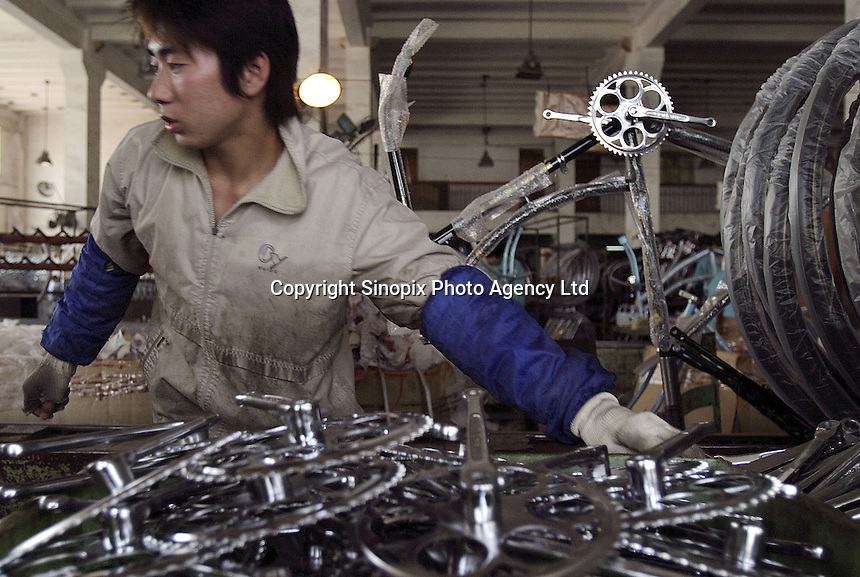 A worker installs componets onto a bicycle at the Shanghai Forever Bicycle Factory (SFBF) in Shanghai, China. Despite the government's efforts to encourage automobile ownership in recent years, the bicycle remains the most popular mode of transportation for China's masses. The SFBF, it's products once a must have and a symbol of status for every Chinese family, are now supplying bicycles to countries around the world. It has seen it's sales increase 59% percent in the past year to 876 million yuan (euro 89.36 million)..21-APR-04