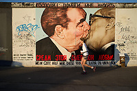 """Jogger running past the remains of the Berlin Wall. Fresco depicting the """"brotherly kiss"""" between Leonid Brejnev and Erich Honecker, East Side Gallery, work by Dmitri Vrubel"""