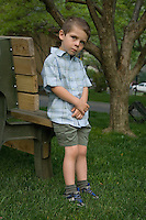 Young boy in green shirt and shorts stands next to wooden bench in yard