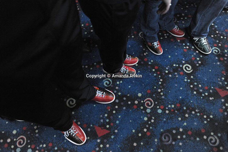 Afghan-American bowlers in bowling shoes stand as they listen to instructions from organizers prior to the kickoff of the Afghan Bowling Tournament in Annandale, Virginia on February 28, 2010.