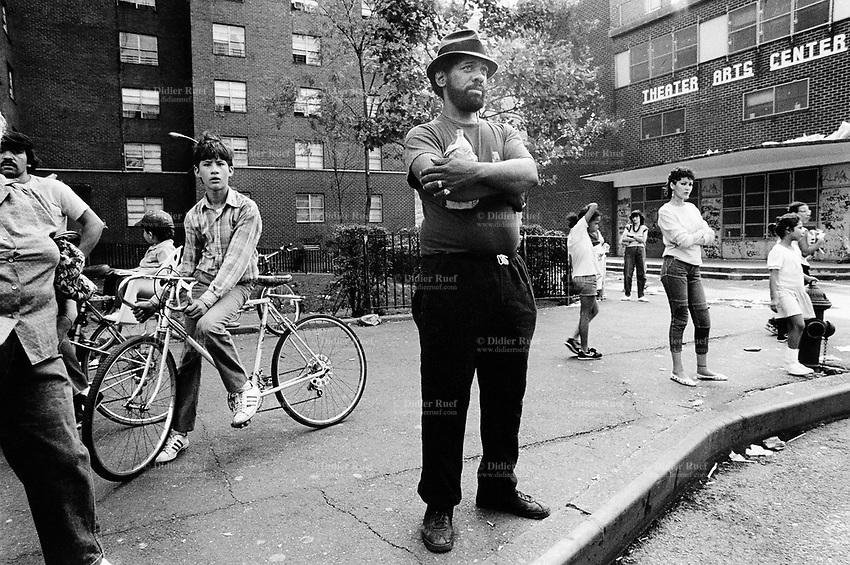 """USA. New York City. Spanish Harlem. Tito (C) stands on 110 Str and holds a bottle of beer in a paper bag. Puerto Rican men and women. Tito lives below the poverty line and receives public assistance (AFDC, Home Relief, Supplemental Security Income and Medicaid). Tito and his family reside in units managed by the New York City Housing Authority (NYCHA) which provides housing for low income residents. NYCHA administers rental apartments in facilities, popularly known as """"projects"""". Spanish Harlem, also known as El Barrio and East Harlem, is a low income neighborhood in Harlem area. Spanish Harlem is one of the largest predominantly Latino communities in New York City. 15.09.86 © 1986 Didier Ruef"""