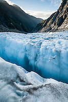 Looking across blue crevasses towards Waiho valley from Defiance Icefall of Franz Josef Glacier when sun sets, Westland National Park, West Coast, World Heritage, South Island, New Zealand