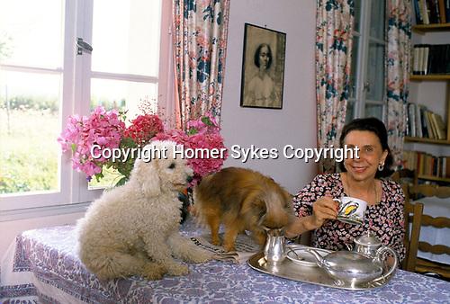 Her Serene Highness Elisabeth de Croy, having tea and with her dogs. France 1980s.