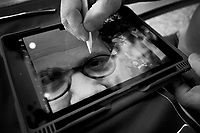 Switzerland. Canton Geneva. Hermance. The artist Robert Nortik is using his iPad tablet to paint on a picture and modify artistically the portrait of Didier Ruef.15.07.2020  © 2020 Didier Ruef