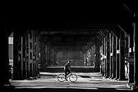 A man rides a bike down Smallman Street past an empty 33rd Street on the edge of the Strip District on Thursday April 2, 2020 in Pittsburgh, Pennsylvania. (Photo by Jared Wickerham/Pittsburgh City Paper)