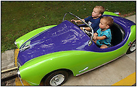 Two young boys try their hand at driving a car at an amusement park.  Model released image can be used to illustrate many purposes.