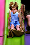 Cindy Swardt, 8, reacts as she rides down the the Super Slide during the annual Arbordaze in Euless, Texas, Saturday, April 27, 2002. (photo by Khampha Bouaphanh)