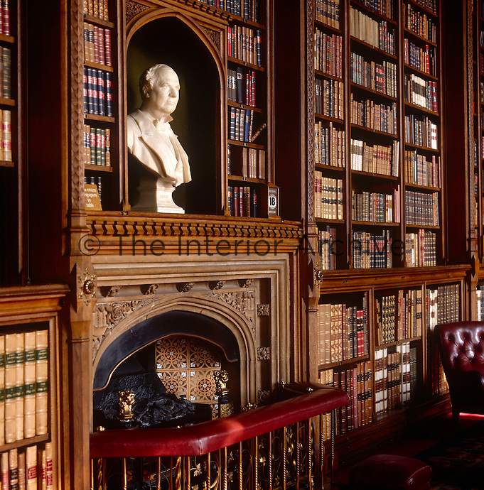 A marble bust above the library fireplace is framed by shelves of gilt-edged leather-bound books