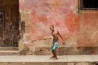 Boy playing stickball in the street