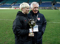 USA Megan Rapinoe holds the trophy of best player next to Thomas Sermanni  after their Algarve Women's Cup soccer match final against Germany at Algarve stadium in Faro, March 13, 2013.  .