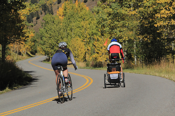 Family biking, with one biker pulling a trailer on Castle Creek Road, Aspen, Colorado, USA .  John offers private photo tours in Denver, Boulder and throughout Colorado. Year-round.