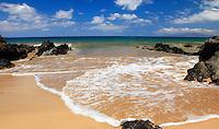 On a warm day, a foamy wave spreads out on Keawakapu Beach, Maui.