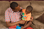 Three year old boy at home sitting with father on couch talking sad mood problem difficulty