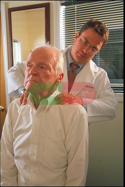 chiropractor examining elder patient's neck