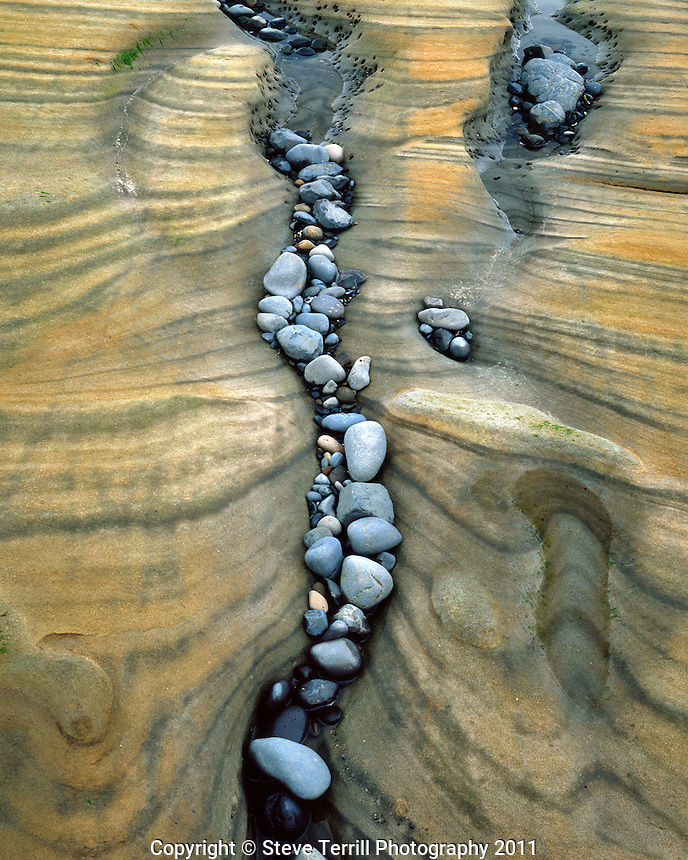 Beach rocks coming to rest in crevices of sandstone formations at Seal Rock Beach, Oregon