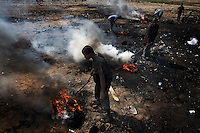 Children burn cables from computers and other electronic equipment in order to retrieve copper, at Agbogbloshie dump, which has become a dumping ground for computers and electronic waste from all over the developed world. Hundreds of tons of e-waste end up here every month. It is broken apart, and those components that can be sold on, are salvaged. Burning creates some of the most carcinogenic and toxic substances known, including polycyclic aromatic hydrocarbons, dioxins and furans, as well as releasing toxic metals such as lead, beryllium and cadmium. At theses burning sites concentrations of toxic metals have been found at over one hundred times the normal level. Children do not wear any protective clothing and so expose themselves to lethal doses of these hazardous chemicals...