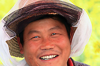 Luoping, Yunnan. Even if the Italian bees are known for their gentleness, the beekeepers protect themselves with a straw hat and veil.