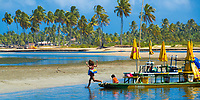 Young kids on a colorful, typical local boat in Porto de Galinhas, with sand beach and palm trees in the background, in Ipojuca Pernambuco, Brazil