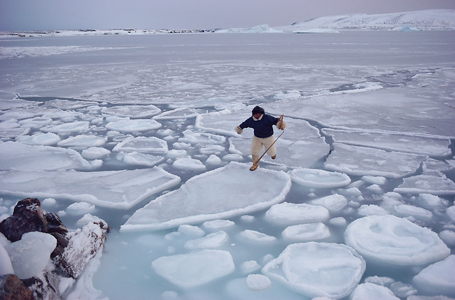Inuit hunter jumps across  pancake ice to get ashore. Savissivik, N.W. Greenland