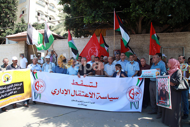 Palestinian supporters of the Popular Front for the Liberation of Palestine, take part in a protest to show solidarity with prisoners on hunger strike in Israeli Jails, in front of the headquarters of Red cross in Gaza city on August 10, 2021. A total of 13 Palestinian prisoners in Israeli detention currently remain on hunger strike in protest of their unfair administrative detention without a charge or trial, according to the Detainees and Ex-Detainees Affairs Commission. Photo by Omar Ashtawy