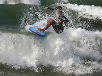 A surfer performs a floater, a maneuver in which the surfer rides over and/or along the top of a breaking wave. Near Biarritz,France.