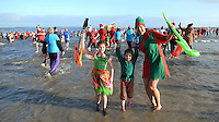 Pictured: A woman with two children in elves outfits take to the freezing cold sea in Tenby, west Wales, UK. Monday 26 December 2016<br /> Re: Hundreds of people in fancy dress, take part in this year's music-themed charity event, the Boxing Day Swim in Tenby, Pembrokeshire, Wales, UK