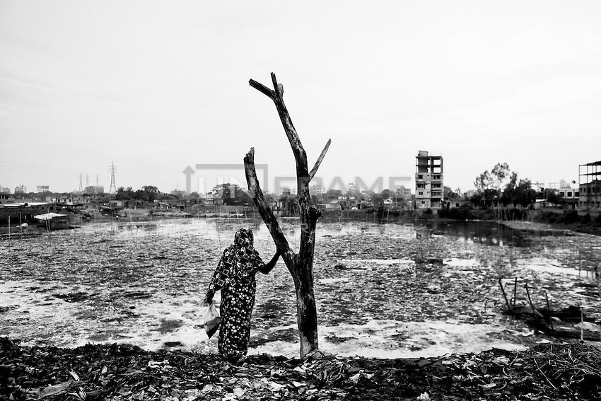A woman stands in front of a pond full with toxic chemical and animal waste at Hazaribagh tannery area in Dhaka, Bangladesh.  Tanneries in the city's Hazaribagh area discharge more than 30000 square meters of liquid waste every day. The tanneries discharge the effluents into the water system causing a large area of acid sludge. Dhaka, Bangladesh.