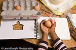 Preschool Headstart 3-5 year olds children doing guided observation and drawing comparing eggs from different mammals child holding chicken egg