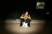 CHINA. Beijing. A woman, eating KFC in the street. 2008