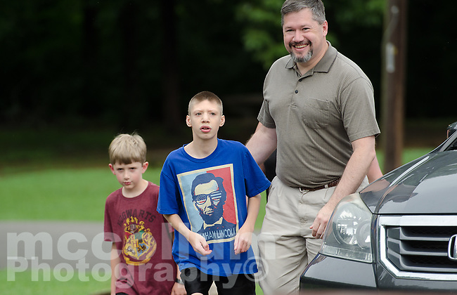 """Michael McCollum<br /> 8/2/18<br /> David Overman arrives with his sons Ryan,13,(middle) and Alex,7, at the reveal ceremony where it was announced to Ryan Overman of west Knoxville that The Wish Connection is granting Ryan's wish to go to Washington DC and visit the White House at Carl Cowan Park, 10058 S Northshore Dr, Knoxville, TN, Thursday, August 2, 2018 at 5:45pm. Approximately 50-60 people attended, including the Overman family, friends, and AT&T Employees. The Bearden High School Cadets also attended and lead the pledge of allegiance.<br /> The AT&T Wish Connection is going to send Ryan, his family, and his service dog to Washington DC and while they are gone, the group of volunteers will be doing a makeover on his bedroom and turn it into the """"Oval Office"""" at the White House.<br /> Ryan was born two weeks prematurely on May 13, 2005. During the pregnancy he was classified as high risk due to a measured lack of growth and, after a brief stay in the hospital, he came home weighing only 4 lbs 5 oz. His development was much slower compared to his peers, such as not learning to walk until he was well over a year old, and he was much smaller. The Overman family worked with Tennessee Early Intervention Services (TEIS) when Ryan was about one year old and with their help they were able to get Ryan enrolled through TEIS to receive Occupational, Physical, and Speech Therapy. When Ryan turned three he transitioned from TEIS to the Knox County Early Intervention Program and began attending a special school to continue his therapies until he was old enough to enroll at Cedar Bluff Elementary and now is at Cedar Bluff Middle School. In 2016, Ryan was diagnosed to have retinitis pigmentosa, a degenerative disease of the retinas that under the best of circumstances causes severe tunnel vision, but more commonly results in complete blindness.<br /> Despite the physical difficulties that Ryan has had to endure over the last thirteen years, he continually brightens the lives """